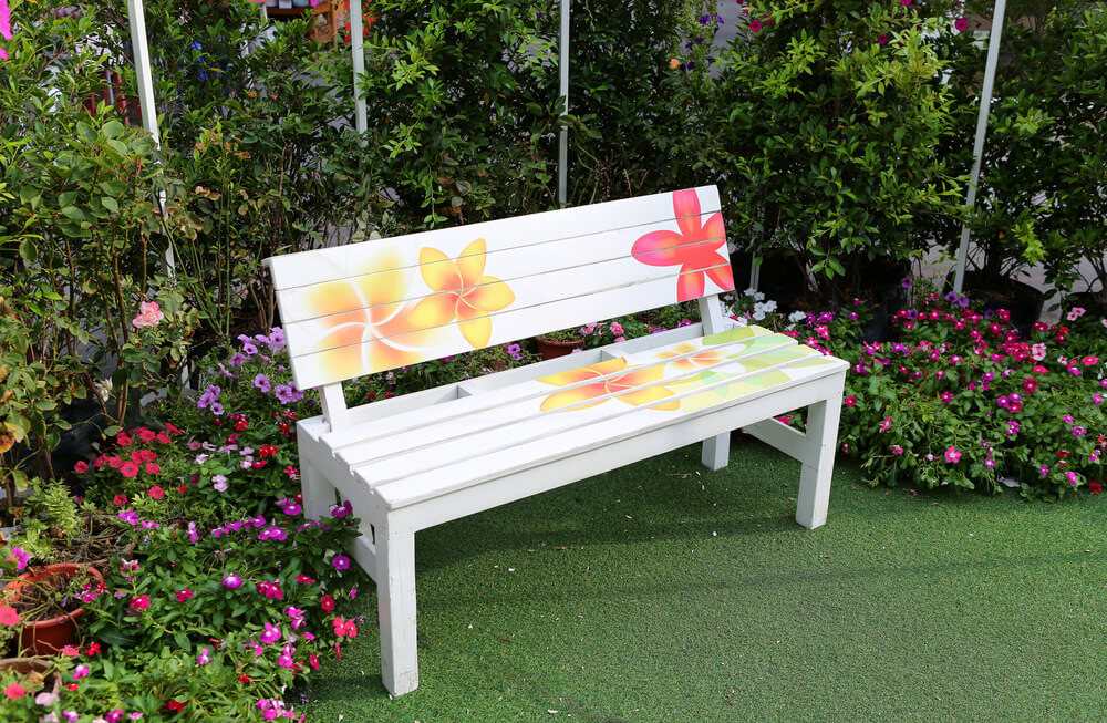 A decorative garden bench is a good match for a colorful garden. This garden bench is painted in white and decorated with flowers on the back rest and seat.