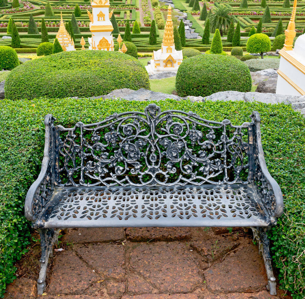 The elegance and style portrayed by this metal garden chair stand up to the elaborate topiary arrangements behind it.