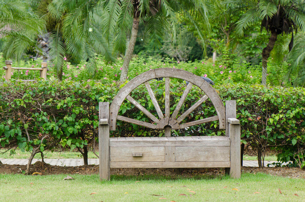 A wooden garden bench with wagon wheel back rest and pull-out drawers under the seat is both functional and decorative.
