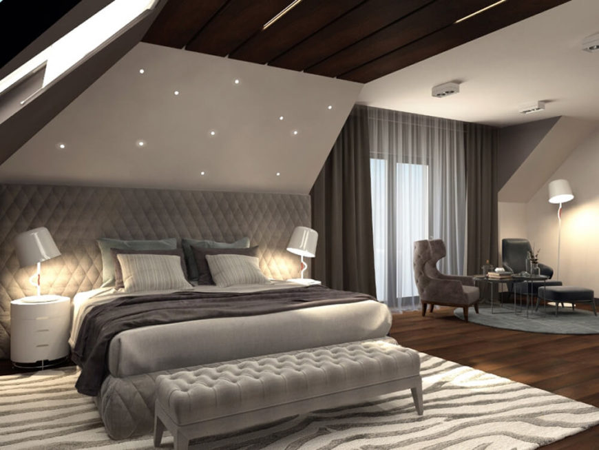 The master bedroom is a huge space, incorporating a sleeping area and distinct relaxing space with armchairs and table. The bed is framed by a massive wall-size headboard and overlooked by star-like embedded lights.