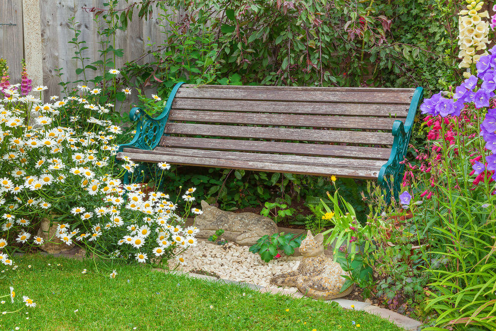A wooden garden bench with metal arms and legs accented with stone cat figures underneath.