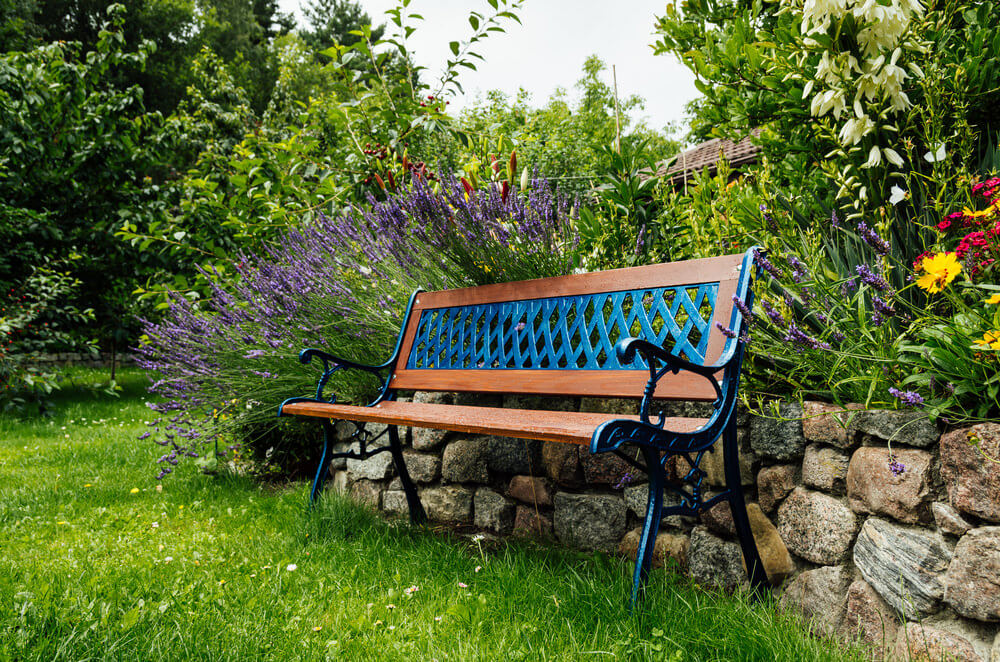 This brand-new metal garden bench has slightly glossy wood framing and bluish metal supports.
