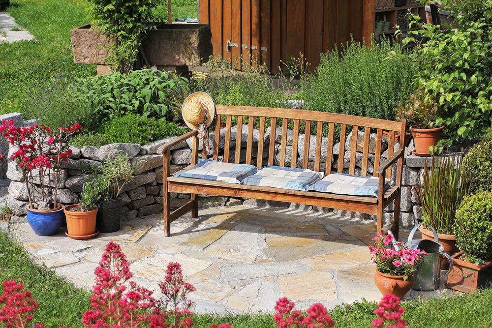 A cushioned wooden garden bench resting on an outside patio with flagstone flooring and a stone wall behind and alongside.
