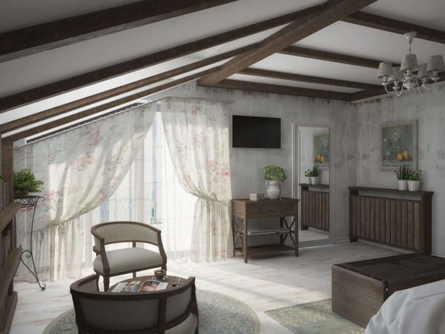 The bedroom features abundant space for relaxing in the sunlight, with a pair of armchairs and coffee table at left.