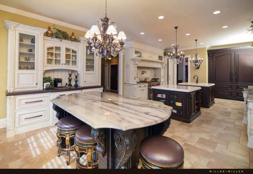 The kitchen is an expansive, richly appointed space with three full islands paired with respective chandeliers. The ornate white cabinetry and dark wood island structures add an elegant sense of contrast.