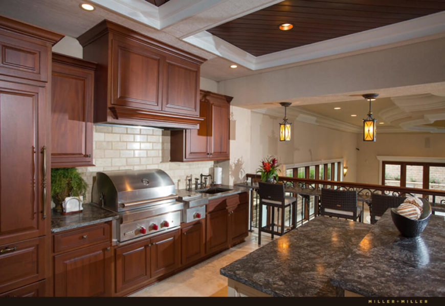 Within this resort-styled end of the home, several important functions are reproduced. Here we see a secondary kitchen with a grill, sink, island, cabinetry, and a great view of the pool area.