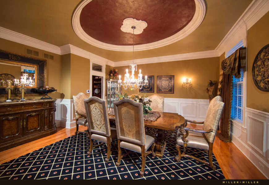 Here we see the luxurious formal dining room, with its intricate flooring that mixes carpet and hardwood. The ornate furniture and carved wood credenza maintain the luxurious atmosphere.