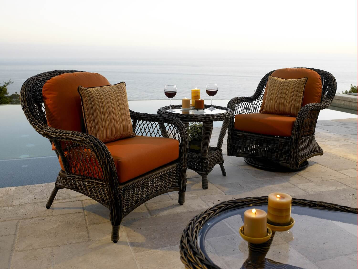 Dark brown wicker patio chairs with dark orange cushions