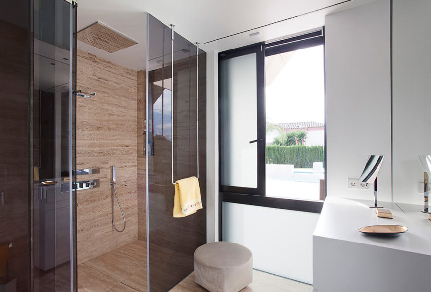 The black glass and marble motif extends into the bathroom where a shower is surrounded with tinted glass and stark white countertops and walls. The monochromatic theme is broken up a bit by the shower tile, but it serves as an accent to the overall design.