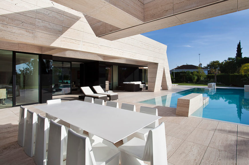 The outdoor eating area has ample seating. It looks out over the minimalistic pool and the black glass and stone facade that adorns the uniquely interesting architecture.