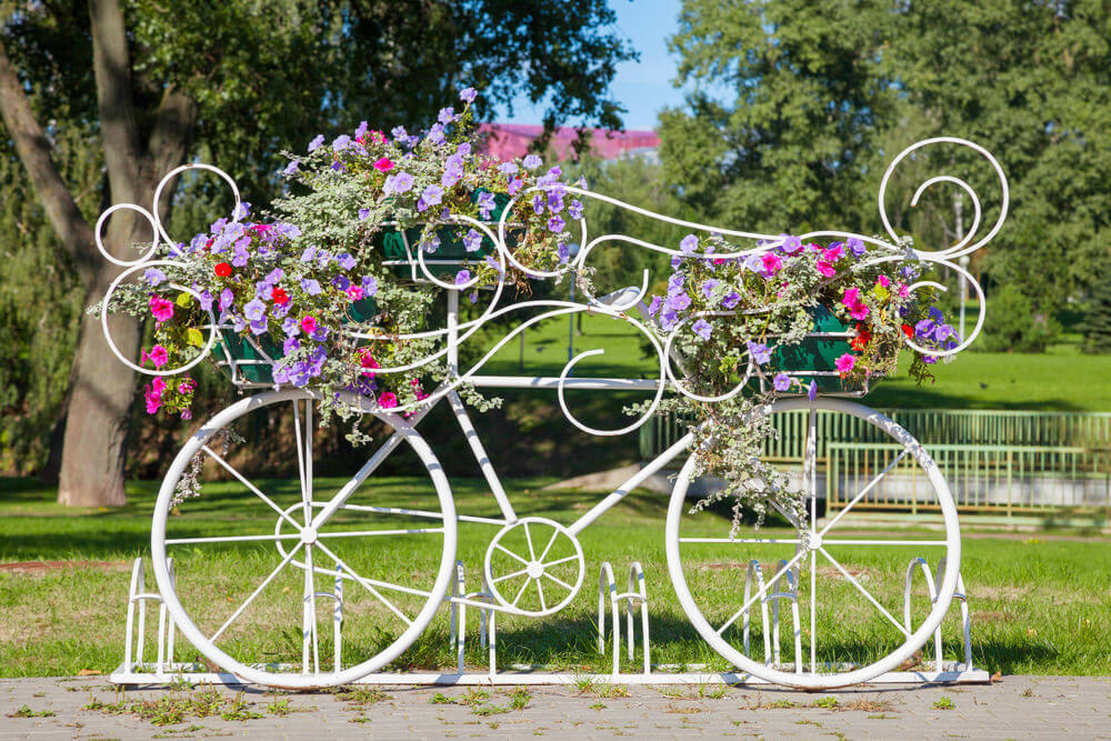 Flower bike sculpture attached to a bicycle stand.