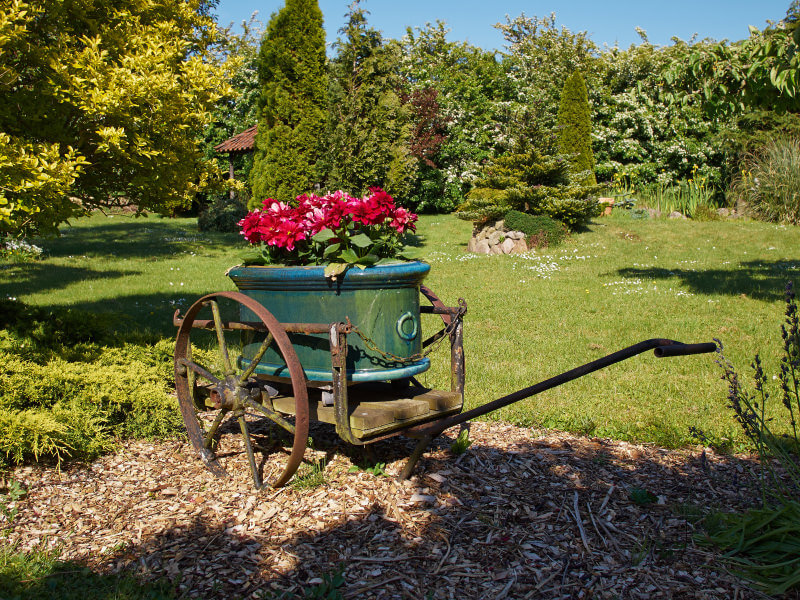 Massive workhorse wagon planter with large metal wheels holding an metal trough-like flower planter.