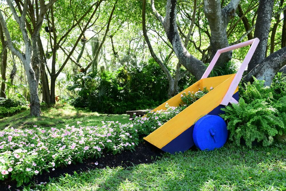 DIY yellow and blue wheel barrow tilted pouring out flower garden.