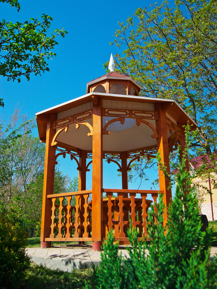 This gazebo is made from rich toned wood with design elements that make it a decorative and beautiful piece where you can sit in the shade and enjoy a meal on a summer day.