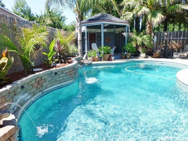 This gazebo sits poolside overtop a couple of relaxing chairs. This spot is a fabulous place to hang out poolside and take it all in. You can slide right into the pool from under the shady gazebo then lay out in the shade and dry off.