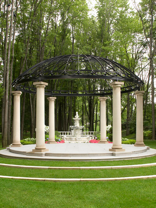 This large gazebo hangs over a fountain and has been placed in front of a garden. This is a decorative structure meant to bring depth and design to the fountain and garden. The gazebo makes the space feel more grand and important.