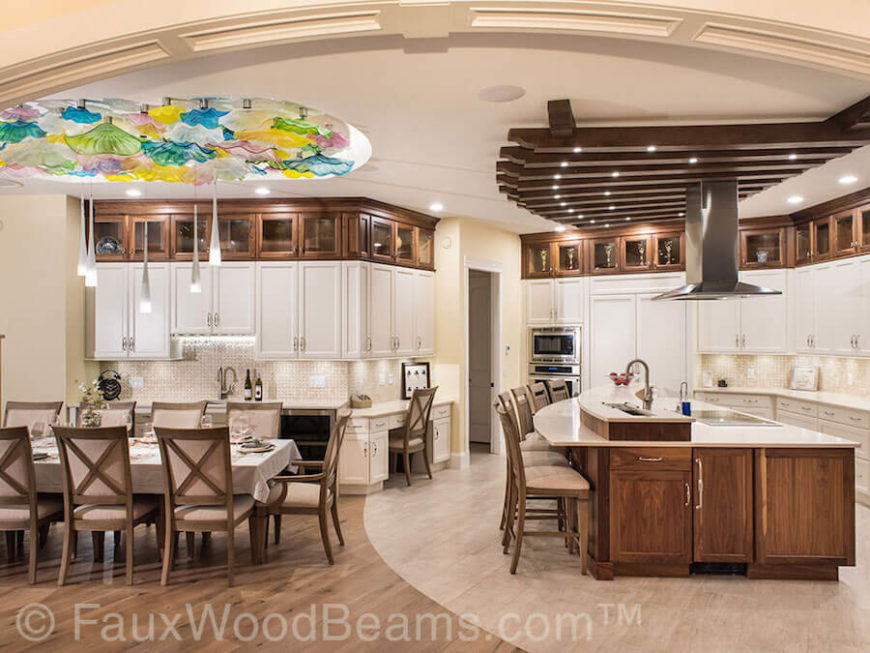 This beautiful kitchen features plenty of natural wood against white  cabinetry and countertops. Faux wooden