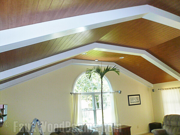 The vaulted ceiling of this room is paneled in wood, and features faux wood beams in a glossy white. It's a great way to add dimension on a tall ceiling.