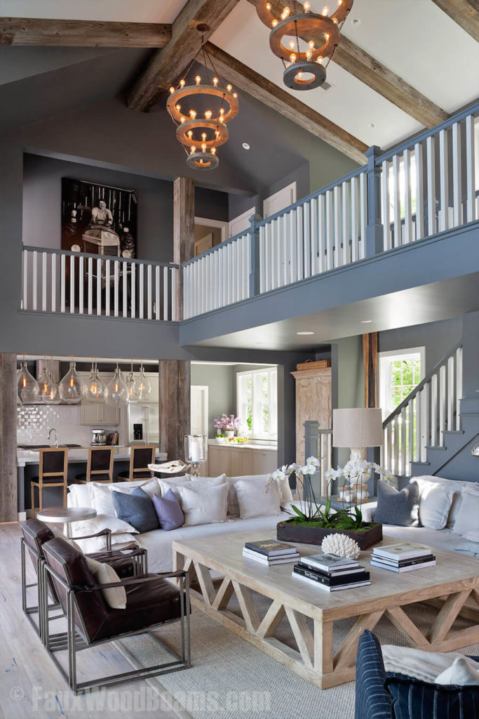 Tall ceilings are perfect candidates for exposed beams, especially faux beams. Here, the beams are above a hallway and living room area, with large chandeliers suspended from the middle beam.