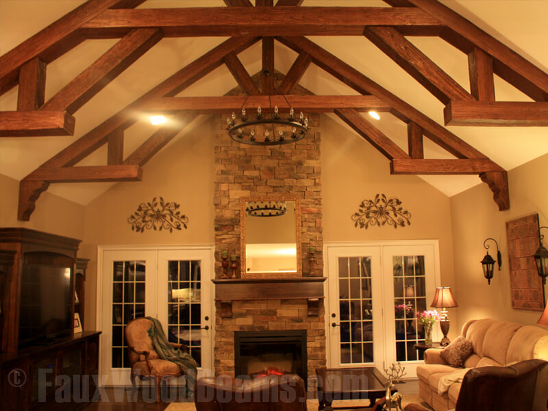 Here we see more A-frame beams, which seem to frame the wooden fireplace flanked by two sets of French doors.