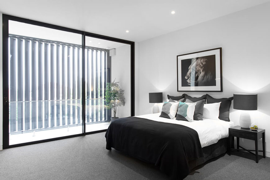 The master bedroom, on the upper level, enjoys private balcony access from a room wrapped in stark black and whites. The balcony gets privacy from public view thanks to the full height louvered panels.