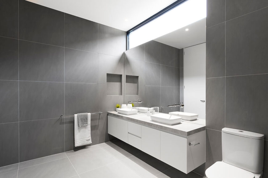 The ultra-sleek bathroom is wrapped floor to ceiling in large format grey tiles, matching the stone countertop on the floating white vanity. Frameless mirror and walk-in shower complete the cohesive look.