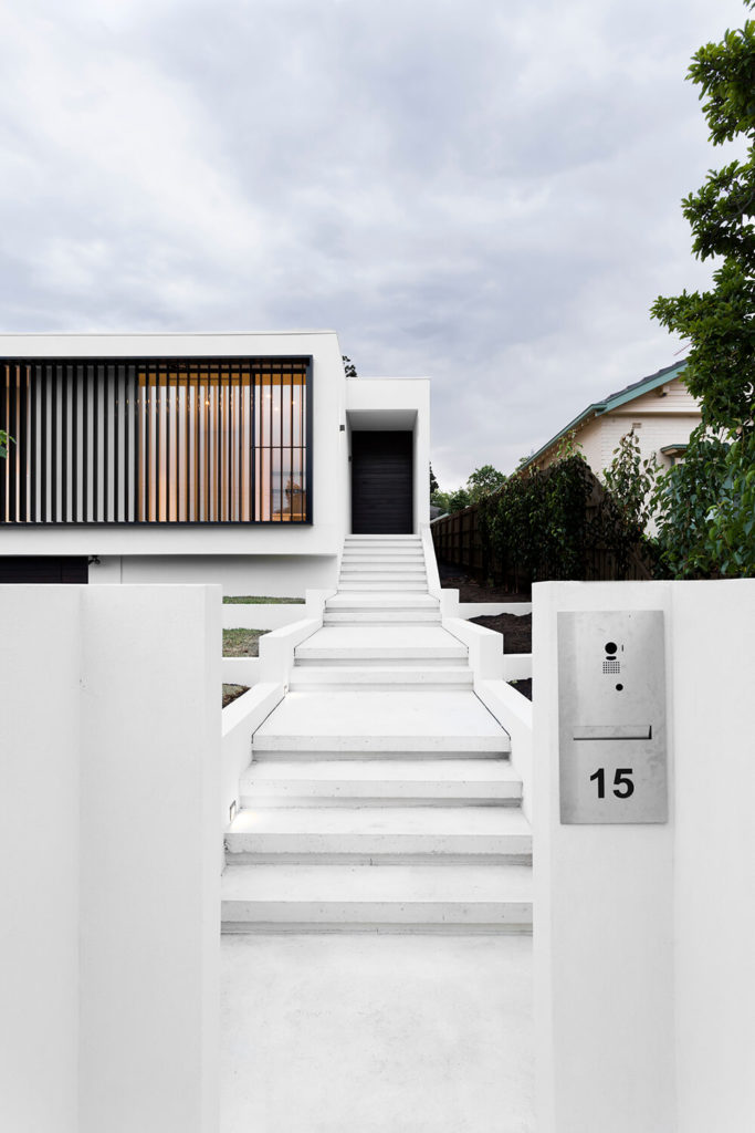 Approaching via the front walk, the home appears to be a simple white box floating above the landscape.