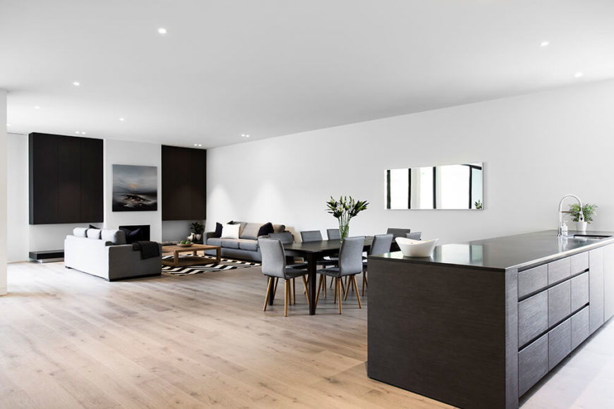 Moving across the vast open space room, we see how the matching sets of varying furniture completes the look. To the right, the massive kitchen island stands out monolithically.