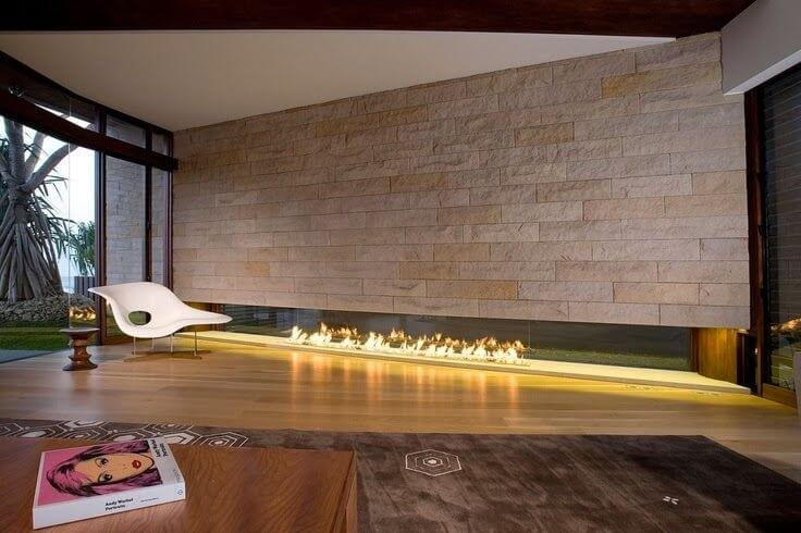 This minimalist room with a modern fireplace is furnished with a La Chaise chair. This space is great for reclining in the fashionable seat with a book while enjoying the fire.