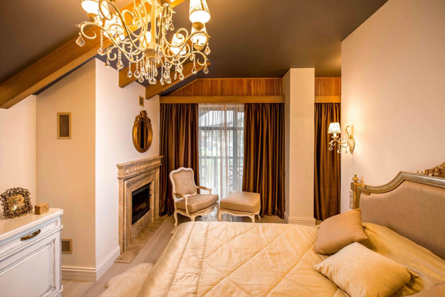The master bedroom features a large marble fireplace and relaxing area, all lit via chandelier and wall sconces. The detailed furniture glows before the large windows and rich wood accents.