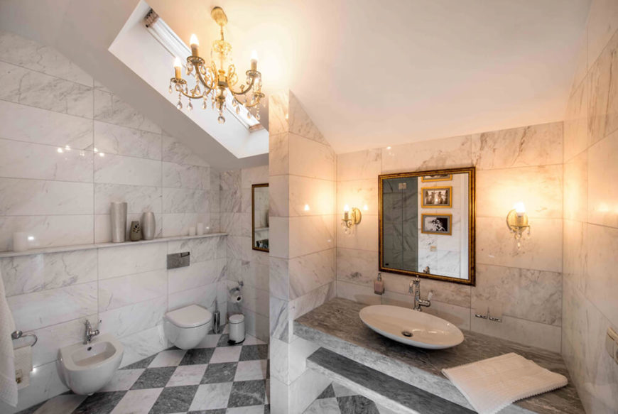 This second bathroom sports a nearly identical look, wrapped in white marble over a checkered floor design. Built-in shelving and a floating vanity make the cozy space feel expansive.