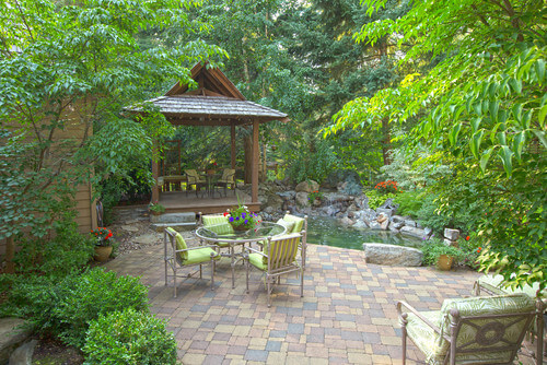 This gazebo sits elevated on this patio, making it so the seating area overlooks the pond and garden off to the side of the patio.