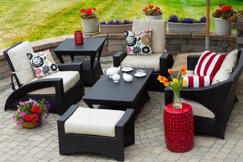 Brick patio with potted flowers among amazing patio furniture.