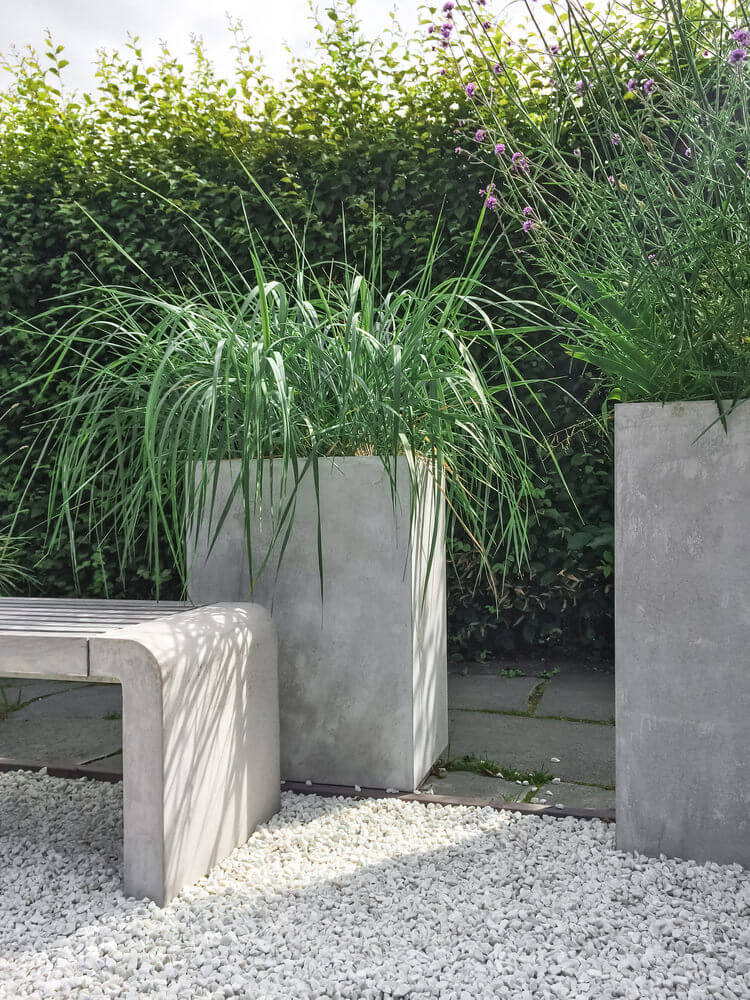 tall modern cement planter holding tall grass on a patio - Tall Potted Plants