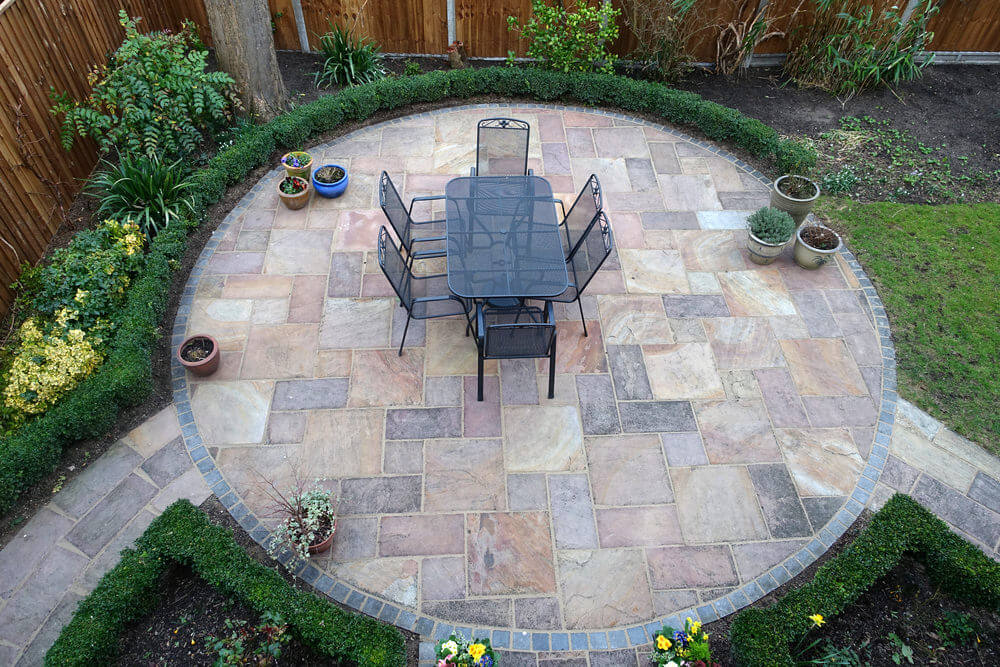 Overhead View Of Round Patio With Potted Plants, Trees And Flowers On The  Outside Of