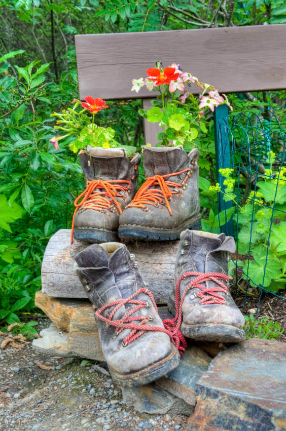 A pair of washed out work boots serve as flower planters while another pair of an even more washed out boots awaits its turn to be revived. The brightly colored laces of both boots add striking contrast to its faded environment.