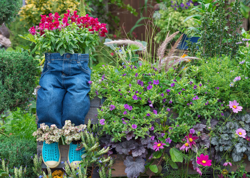 A pair of trousers looking as if sitting on a wooden fence is used as a flower planter. A pair of crocs, also used as flower planters, are connected right beneath the trousers, with the flowers springing up both create a playful vibe to this flower garden.