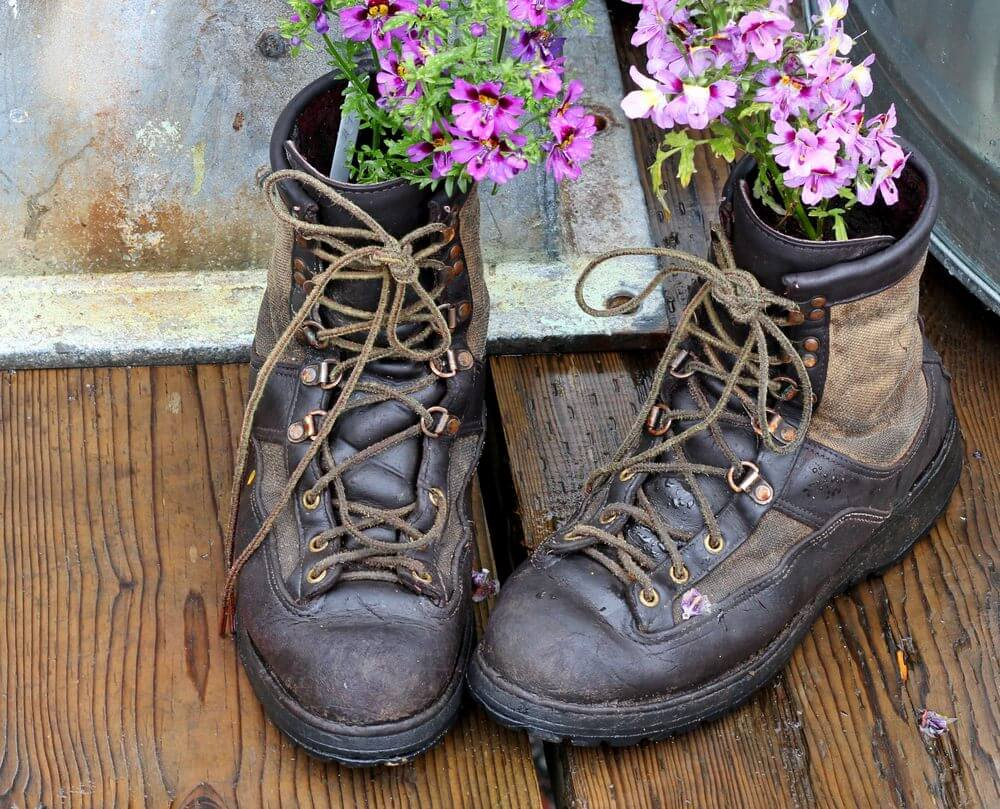 This pair of wet-looking and worn out tactical boots has had its days of action. They still look masculine enough but completely domesticated as they're used to hold flowering plants.