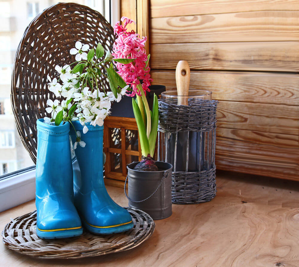 A clean-looking, brightly colored pair of gumboots used as flower planters can also look harmonious indoors. The bright blue color of these gumboots and the whiteness of the flowers altogether invite a cheerful atmosphere.