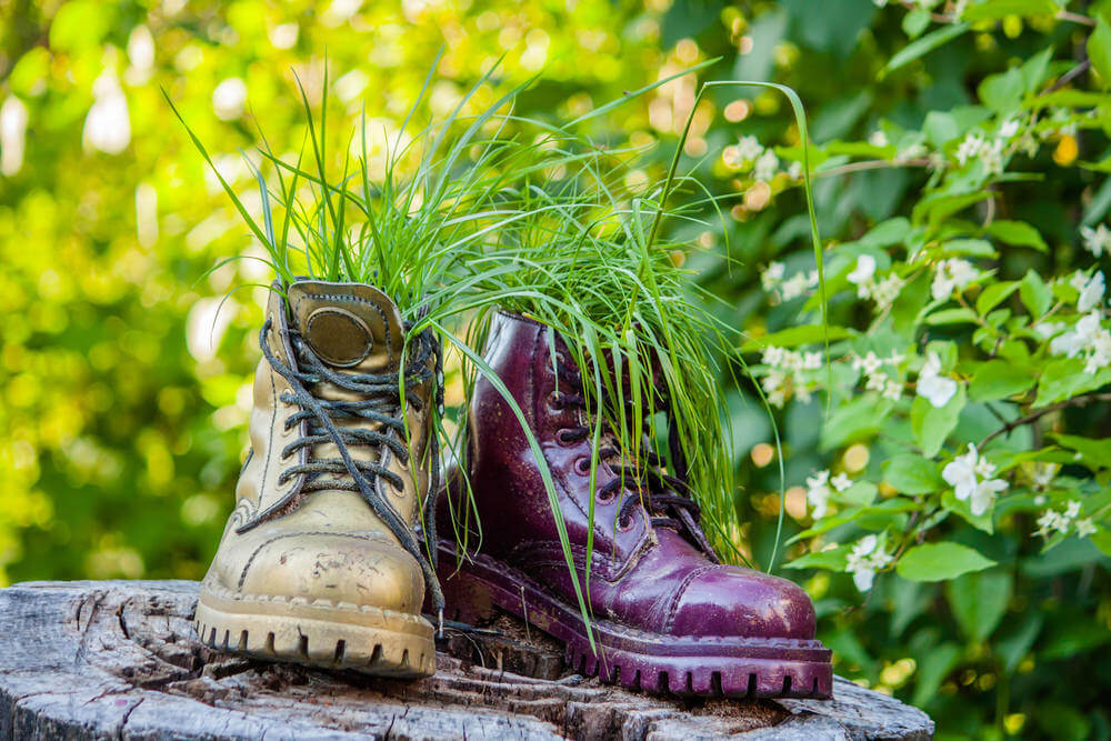 If you want to create a more artistic piece, choose a couple of discarded boots that you can use as planters, spray them with funky shiny colors, and then display them on a cut-up tree trunk.