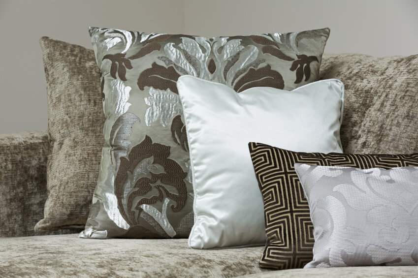 Brushed dark green and light grey sofa pattern with similar pillows in tone. This pillow arrangement is spiced up with a couple glossy pillow fabrics to offset the flat brushed sofa fabric.