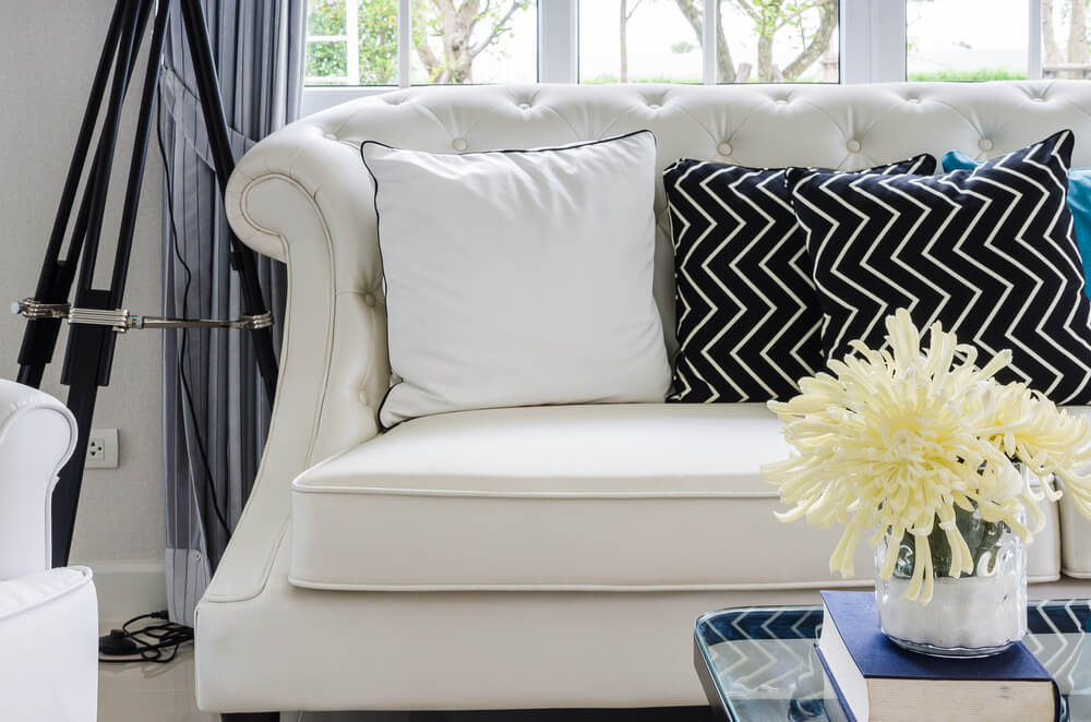 Beautiful White Sofa With A White Pillow And Black Pillow With White Crooked Lines.  The Black