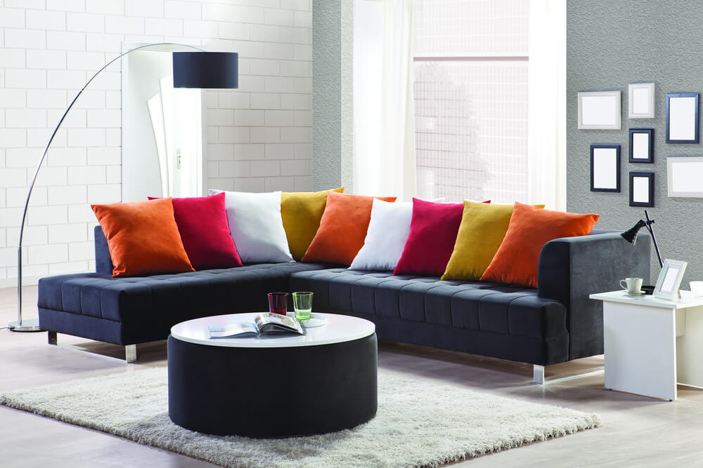 Example of dark blue sectional sofa lined with many bright, solid throw pillows - orange, red and white - in a repeating pattern.