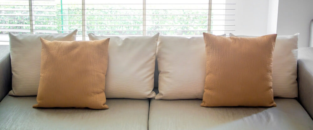 Sofa With Throw Pillows Lined Along The Back With 2 Brown Pillows On Top  For A