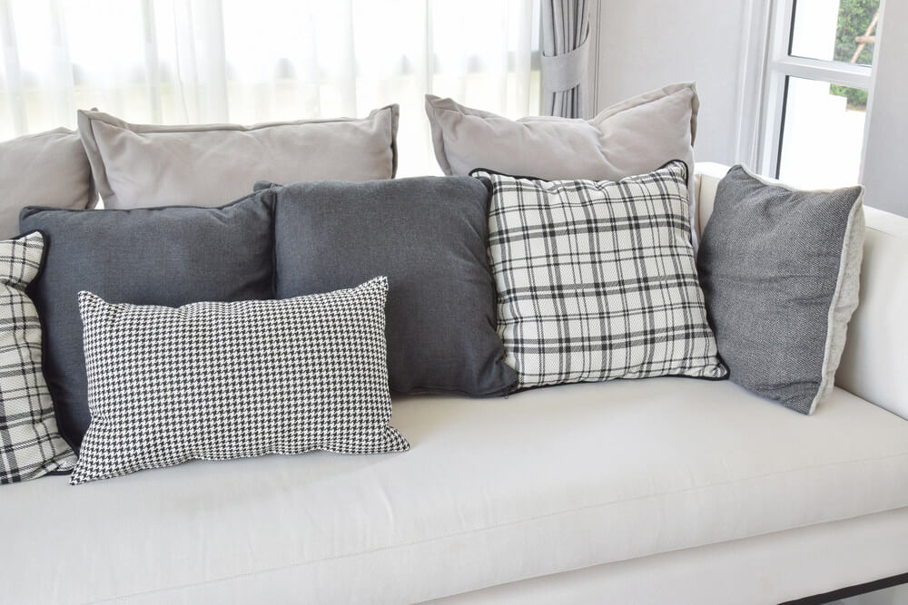 White sofa with charcoal grey and white throw pillows in a variety of patterns including geometric, patterned and solid.