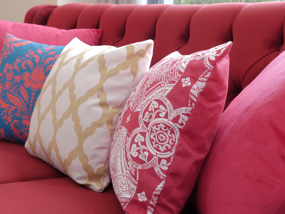 Bright red sofa with heavily patterned throw pillows in matching color, white, light brown and blue.