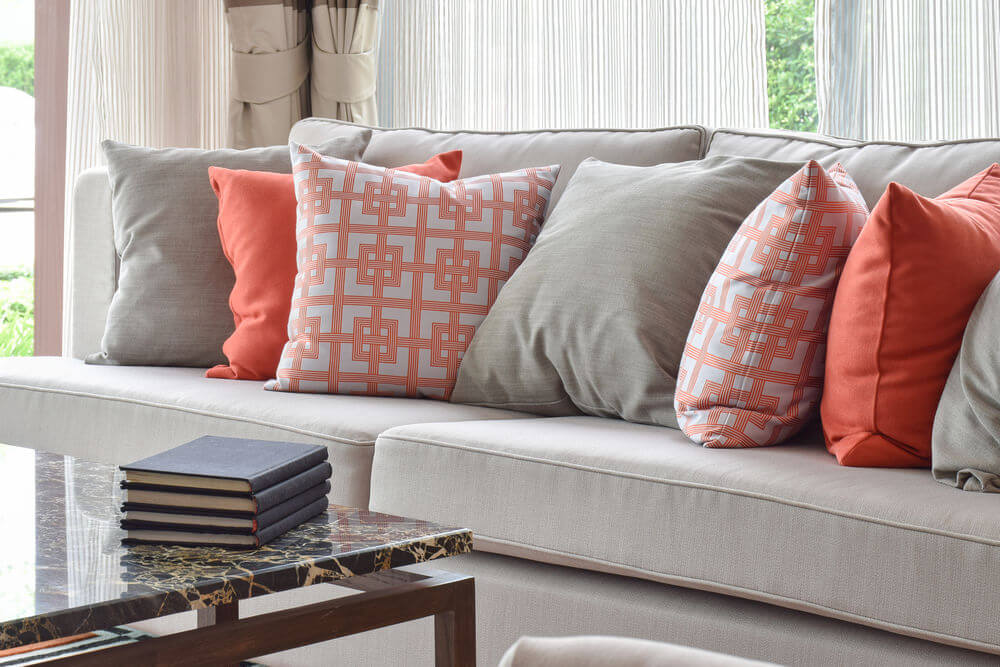 Superb Light Grey Sofa With A Mix Of Bright Orange And Matching Solid Grey Throw  Pillows.