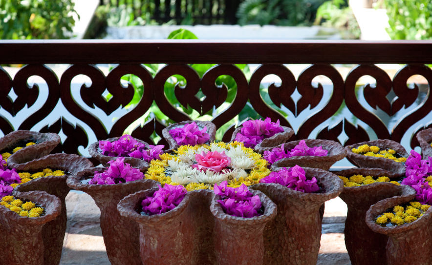 A Large Cluster Of Yellow And Purple Flowers In Ceramic Pots On A Patio  With A