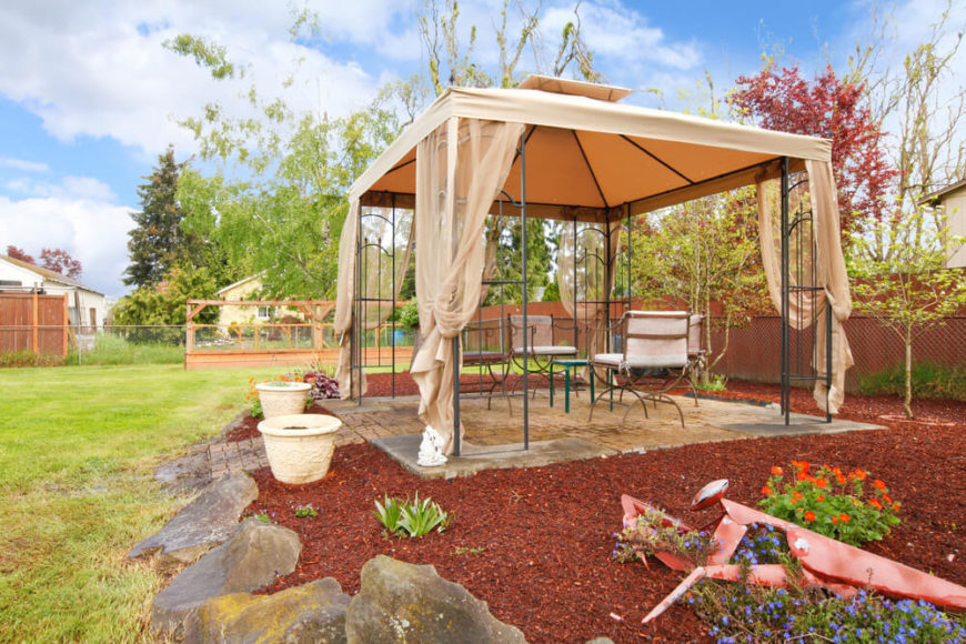 The delicate aluminum frame of this gazebo is covered by sheer curtains and a two-tiered canvas roof. It sits comfortably on a stone patio in the midst of this backyard, a great retreat from the heat of the summer day.