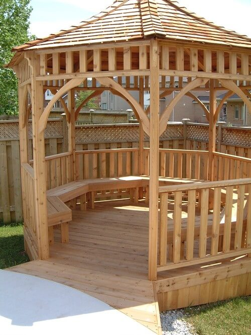 This wooden gazebo sits off the side of a patio and has built in benches that wrap around the inside. These chairs provide ample seating for many people to relax in comfort in the shade.